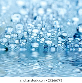 Blue droplets reflected in the water