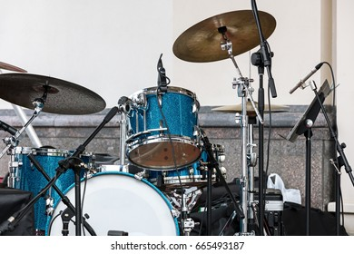 blue drum set and cymbals standing on outdoor stage against wall background