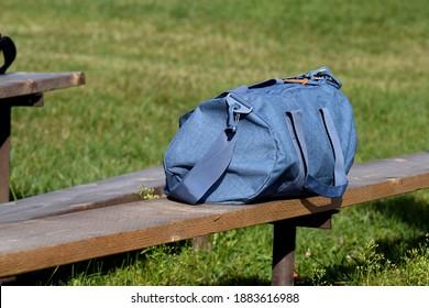 A blue duffel bag on a bench.