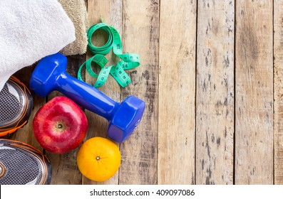 Blue dumbbell, white towel, measuring tape and red apple on wooden table. Fitness concept