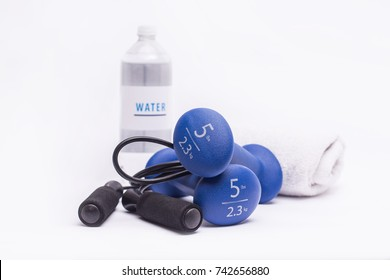 Blue dumbbells with jump rope and water on isolated white background