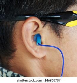 Blue ear plug into the ear.