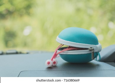 blue earphone case and pink earphone on dashboard car