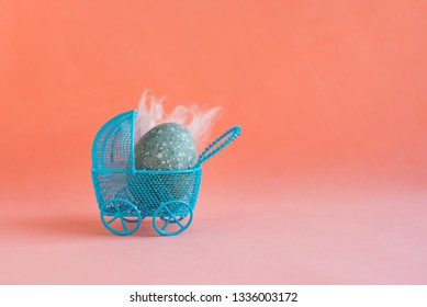 Blue Easter egg with white feathers as a baby lies in a decorative miniature blue baby carriage on a red coral background