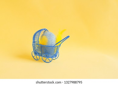 Blue Easter egg with yellow feathers as a baby lies in a decorative miniature blue baby carriage on a yellow background