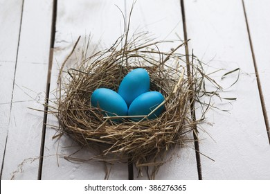 Blue Easter eggs in nest on wooden background