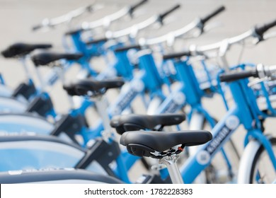 Blue e-bikes or bicycles in a row at a rental station or a shop - selective focus