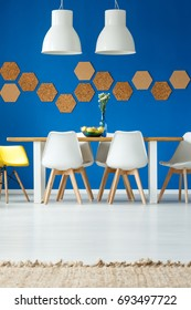 Blue eco dining room with natural cork wall decor, wooden family table, mismatched white chairs and pendant lamps