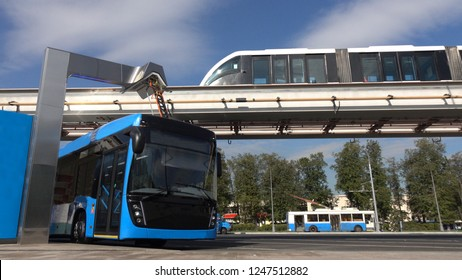 Blue electric bus at the charging station.Modern trains on the monorail.