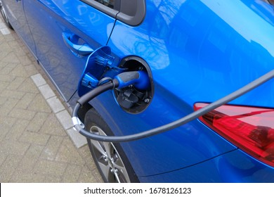 Blue electric car being charged at charging station