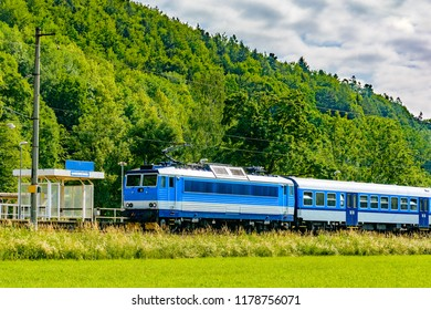 A blue electric locomotive passing the Czech countryside. A train running through the green valley. Rail transport in the Czech Republic. A sunny day on the railroad