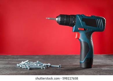Blue electric screwdriver and bolts on wooden table. close-up. Red background.