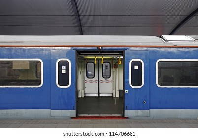 A blue electric train carriage with an open sliding mechanical door at a train station platform.