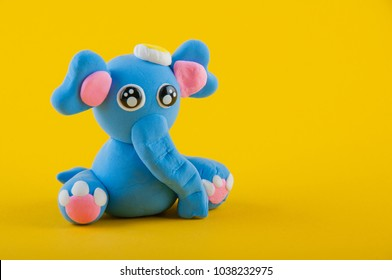 Blue elefant made of modelling clay sitting on yellow background. Space for text