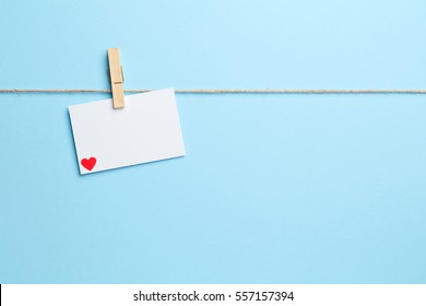 Blue empty background with sting clothes peg and love letter