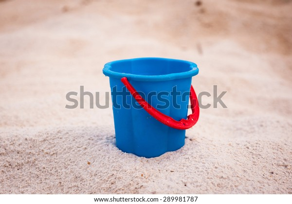 blue empty bucket with red handle, summer, sand.