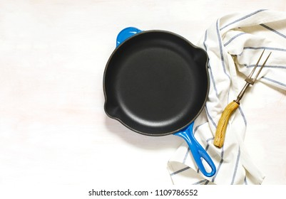 Blue empty cast iron frying pan and meat fork on white background, top view, copy space