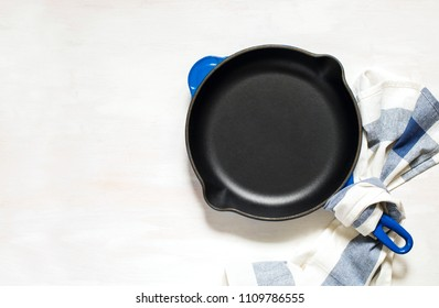 Blue empty cast iron frying pan on white background, top view, copy space