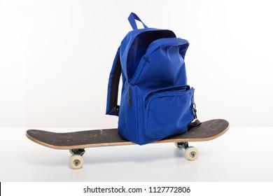 Blue empty open backpack on top of skateboard