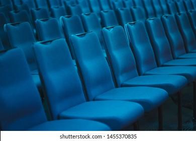 Blauer leerer Sitzplatz im Publikum, vorbereitet für die Teilnehmer der Konferenz oder Präsentation. Organisation und Veranstaltung von Massenveranstaltungen. Weiche, leere Stühle in einer Reihe.