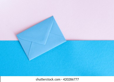 The blue envelope on pink and blue background. Top view.