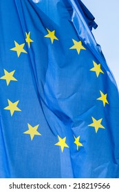 blue european flag with twelve yellow stars blowing in the wind