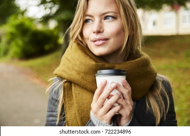 Blue eyed blond woman with coffee in park, looking away