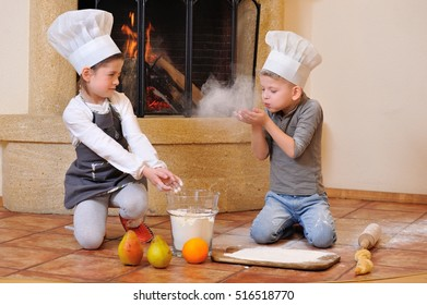 Blue eyed kids in chef's hats near the fireplace: girl dressed in a toque playing cook with her cousin, they are stained with flour, throw and blowing flour from their hands keep sprinkle each other