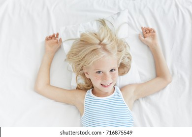 Blue eyed pleasant looking small child in pyjamas, looks happily as has marvelous dreams at night, feels comfort. Joyful female kid with freckles smiles pleasantly before sleep. Good morning
