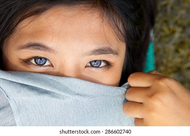 Blue eyes of asian girl using soft lens