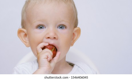 Blue eyes baby eating red raspberry, child offering food, dirty funny kid face
