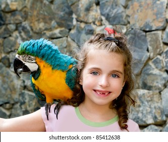 blue eyes child girl with yellow parrot in her shoulder
