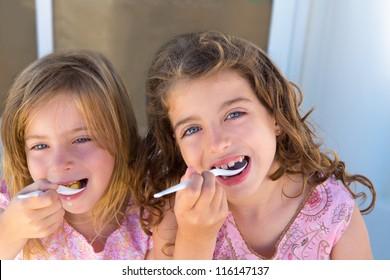 Blue eyes kids sister girl eating breakfast with spoon