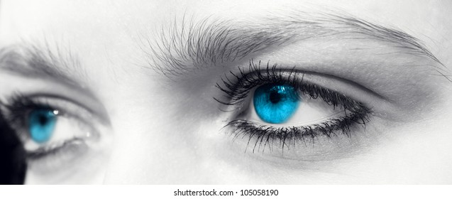 Blue eyes of a young woman in black and white.