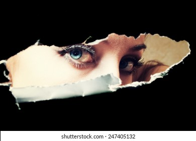 Blue eyes of young woman peeping through a hole closeup