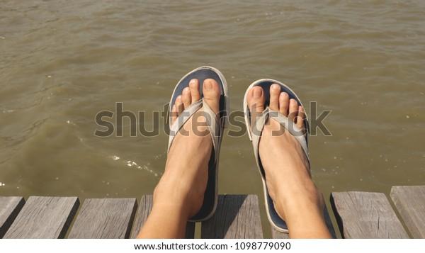 Blue Fabric Flip Flops on Wooden Dock - Muddy Rough Water