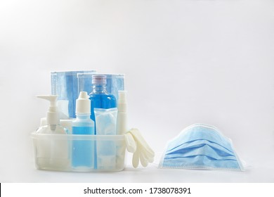 Blue face masks, alcohol, pump, saline bottle, gel, spray, tissue roll and gloves are in a clear box.  A shaped mask is by the set. The hygiene items are essential to prevent Corona virus (Covid-19).