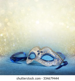 blue female carnival mask and glitter background