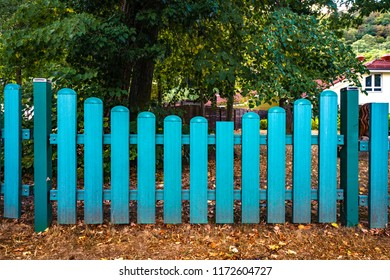 Blue fence gate  at a yard in the fall with trees in the background