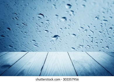 Blue filter - Abstract rain drops on a window or water drops on grass and wood background