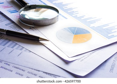 Blue filter effects images of pen and magnifying on financial graph chart.For business concept.