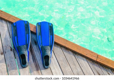 Blue fins for diving on a wooden pier against the background of azure water