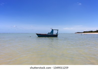 A blue fishing boat at São Miguel dos Milagres, Alagoas, Brazil. A beach called Toque (praia do toque). Fantastic landscape, great beach with clear water. Paradise beach, blue sky.