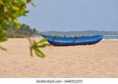 Blue fishing boat on shore sand beach