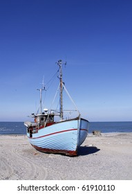blue fishing cutter on shore