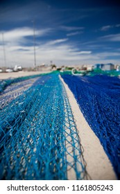 Blue fishing nets stretched out on the floor of a jetty in a port in the Mediterranean Sea