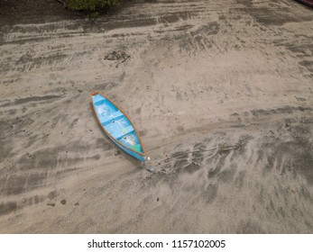 Blue fishing skiff lays on a sandy beach at low tide near Paquera Costa Rica on the Gulf of Nicoya in this aerial drone image