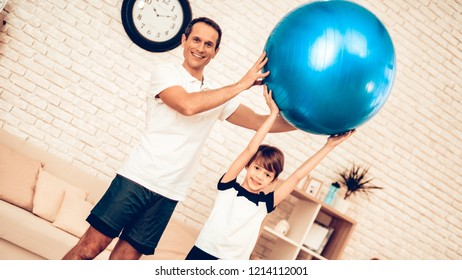 Blue Fitball. Sport at Home. Gym Mat. Doing Sports. Man and Boy Train at Home. Health Concept. Healthy Lifestyle. Swiing Press on Floor in Apartment. Man and Boy with Fitball. Swing Press on Fitball.