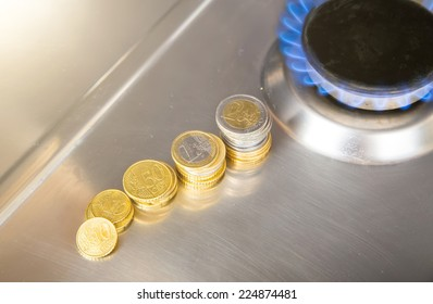 Blue flames of natural gas burning from a gas stove with euro coins