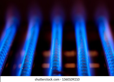 Blue flames of natural gas burnning inside of a boiler furnace - fossil fuel use concept